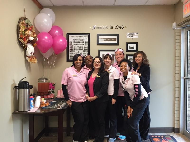 team smiling for breast cancer awareness month